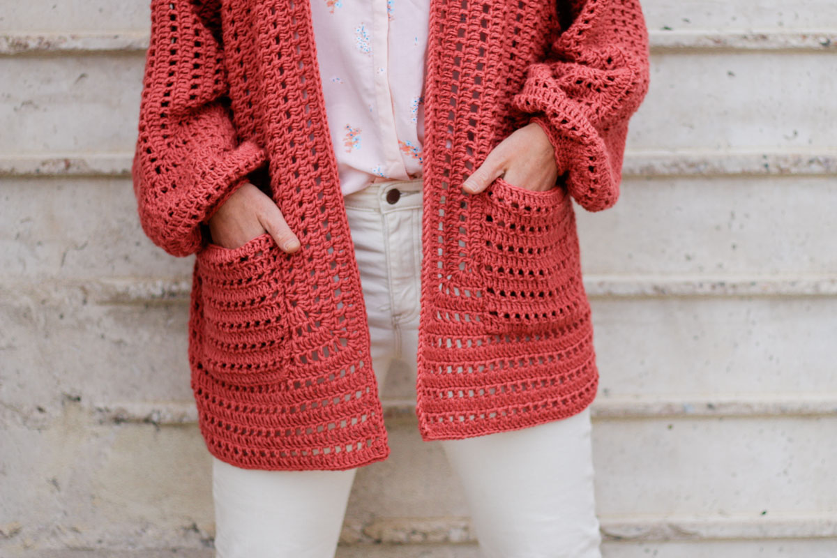 Woman's torso with her hands in the pockets of the easy crochet sweater she's wearing.