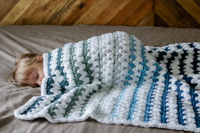 Learn how to make a beginner crochet baby blanket with this easy free pattern and tutorial. You'll be left with very few ends to weave in and a blanket that's as soft as a baby's...well, you know. Get the free pattern featuring Lion Brand Mandala Yarn and Baby Soft Boucle.