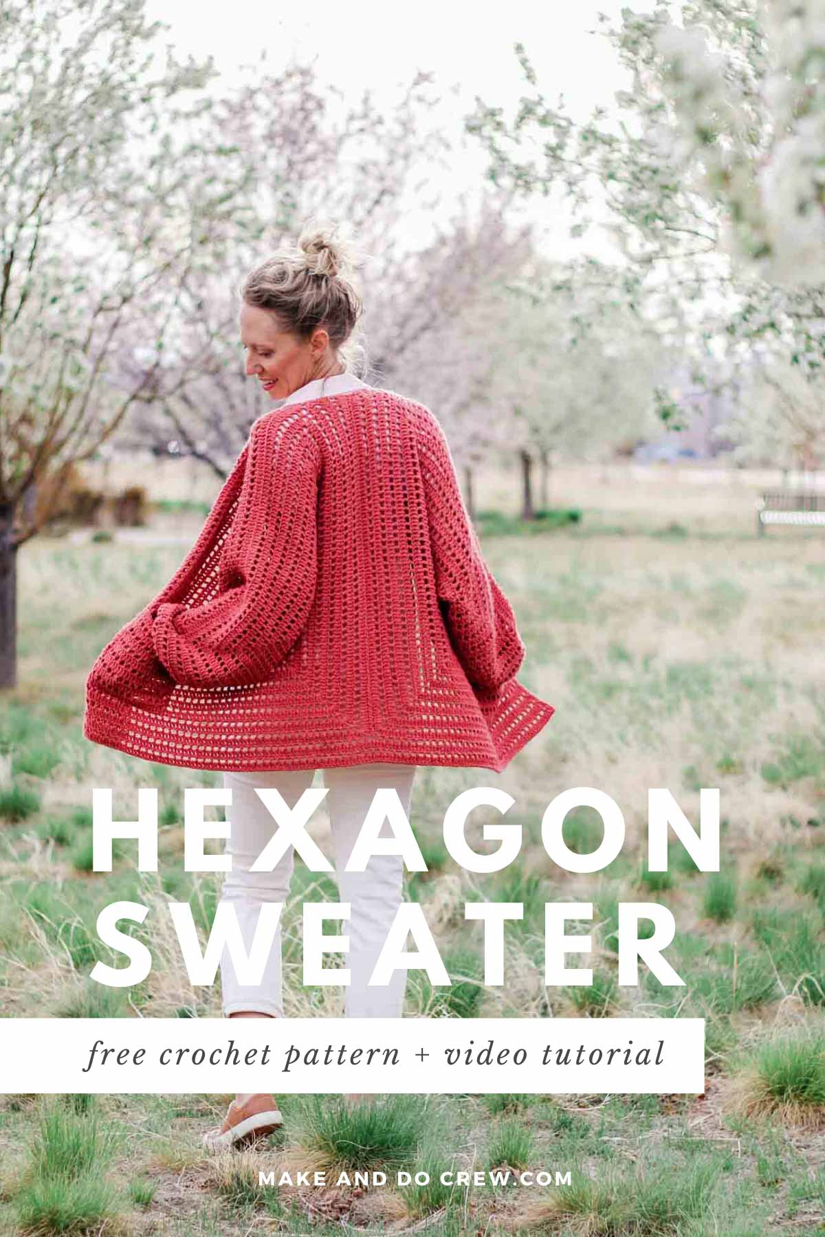 A woman standing in a field of cherry blossom trees wearing a crocheted hexagon cardigan with pockets.