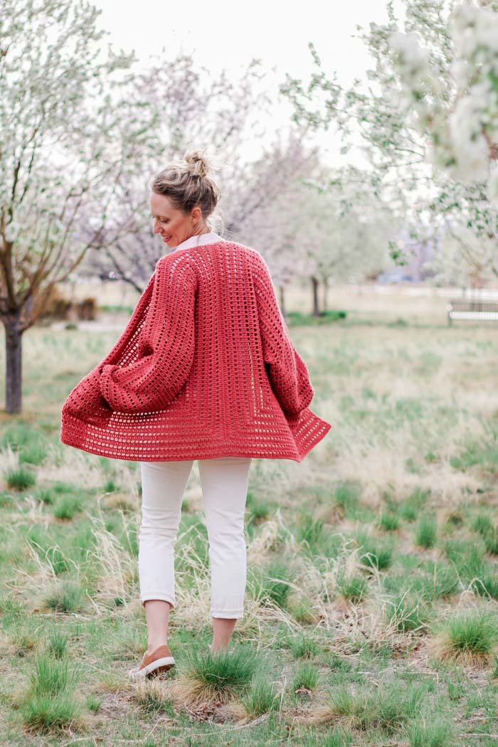 Two simple crochet hexagons transform into a lightweight, on-trend cardigan complete with cozy pockets and roomy bishop sleeves. This easy crochet sweater pattern and tutorial makes a great first garment for beginners and is perfect to wear in the spring or summer.