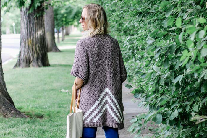 Corner to corner crochet (c2c) short sleeved cardigan with triangle, tribal stripes on back. Free pattern featuring Lion Brand ZZ Twist yarn.