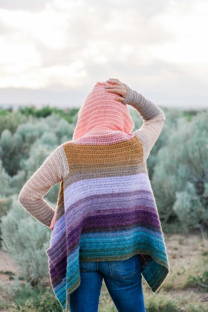 WOW! This beautiful draped cardigan is made by remixing cakes of Lion Brand Mandala yarn to form new gradient stripes. There are very few ends to weave in on this beginner-friendly free pattern and tutorial.
