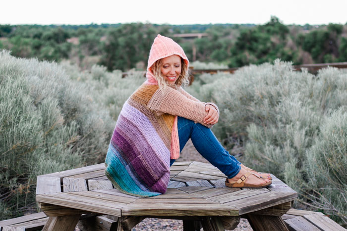 This rainbow gradient crochet cardigan includes pockets and a hood and is made with Lion Brand Mandala cake yarn.