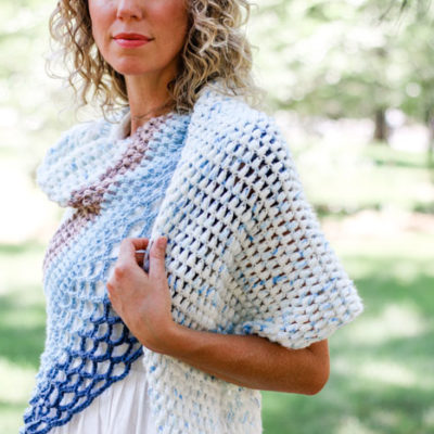 This easy asymmetrical crochet shawl pattern is made from simple puff stitches and lace. Featuring Lion Brand Ice Cream and Mandala yarn.