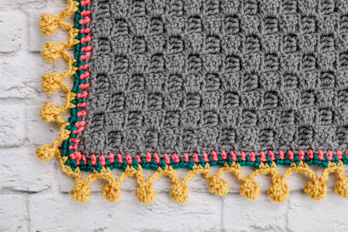 How to crochet a pom pom edging or bobble stitch border on a modern crochet afghan or blanket.