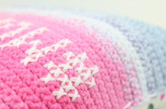 Close up of cross stitch on crochet fabric using Lion Brand Mandala Yarn.