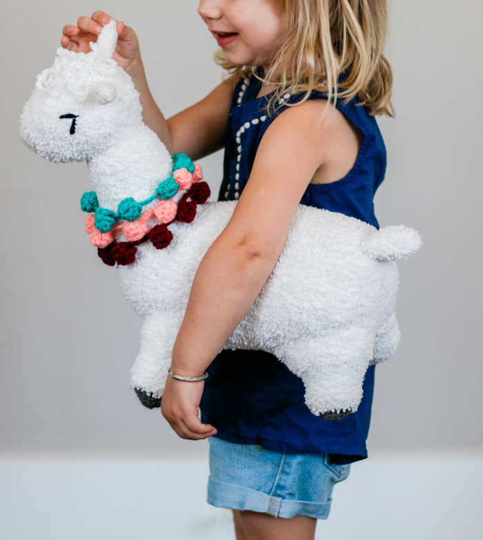A young child holding a crochet alpaca toy made by hand. Free crochet amigurumi llama pattern featuring Lion Brand Baby Soft Boucle yarn.