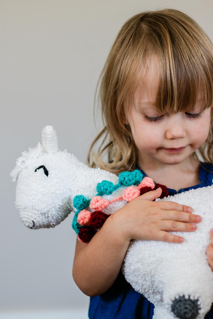 A young child holding a crochet alpaca toy made by hand. Free crochet amigurumi llama pattern.