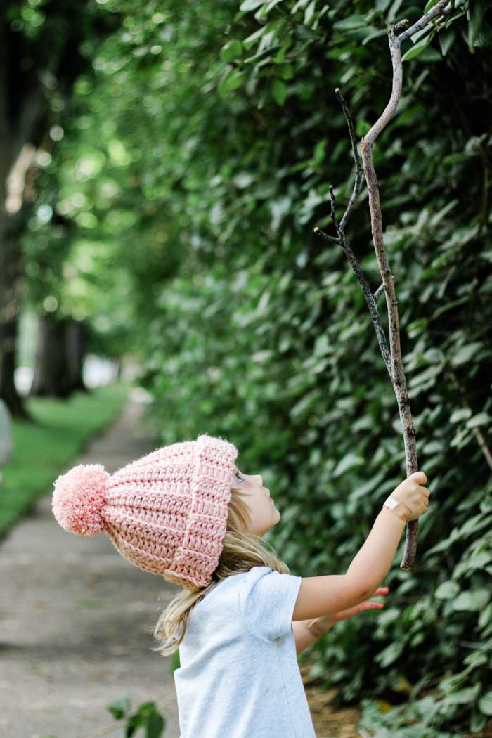 Super beginner-friendly ribbed crochet beanie with a pom pom on a child playing outside. Free pattern and tutorial.
