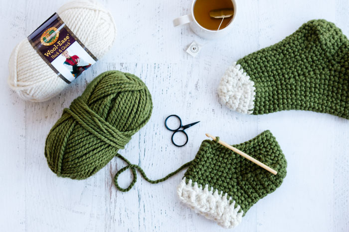 "Free crochet slipper socks pattern using Lion Brand Wool-Ease Thick & Quick chunky yarn in the color ""Cilantro."""