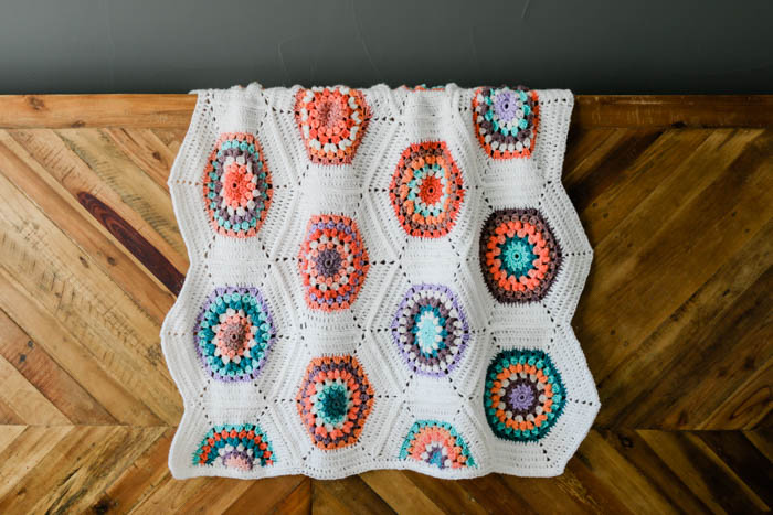Vintage-looking, gender neutral crochet blanket pattern made from crochet hexagons that are joined as you go. Free pattern + video tutorial featuring Lion Brand Mandala, Cupcake and Pound of Love yarns.