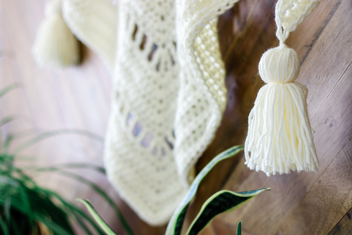 Close up of bohemian crochet wrap with chunky tassels.