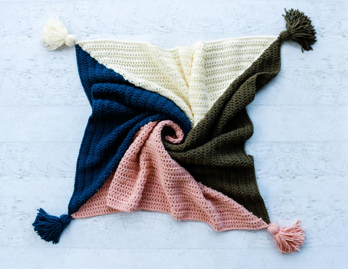 Easy and free four color crochet square blanket pattern with baby and throw sizes included. Perfect tasseled blanket for modern nurseries or decor.