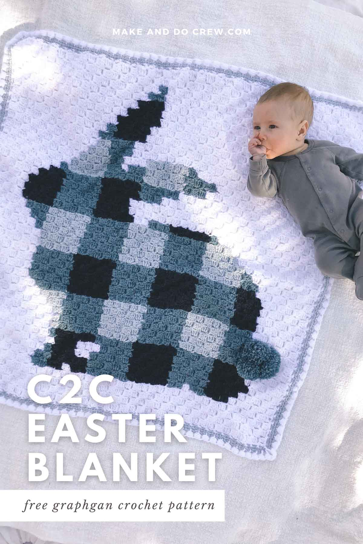A baby laying on a corner to corner crochet bunny blanket that is make with a blue plaid pattern.