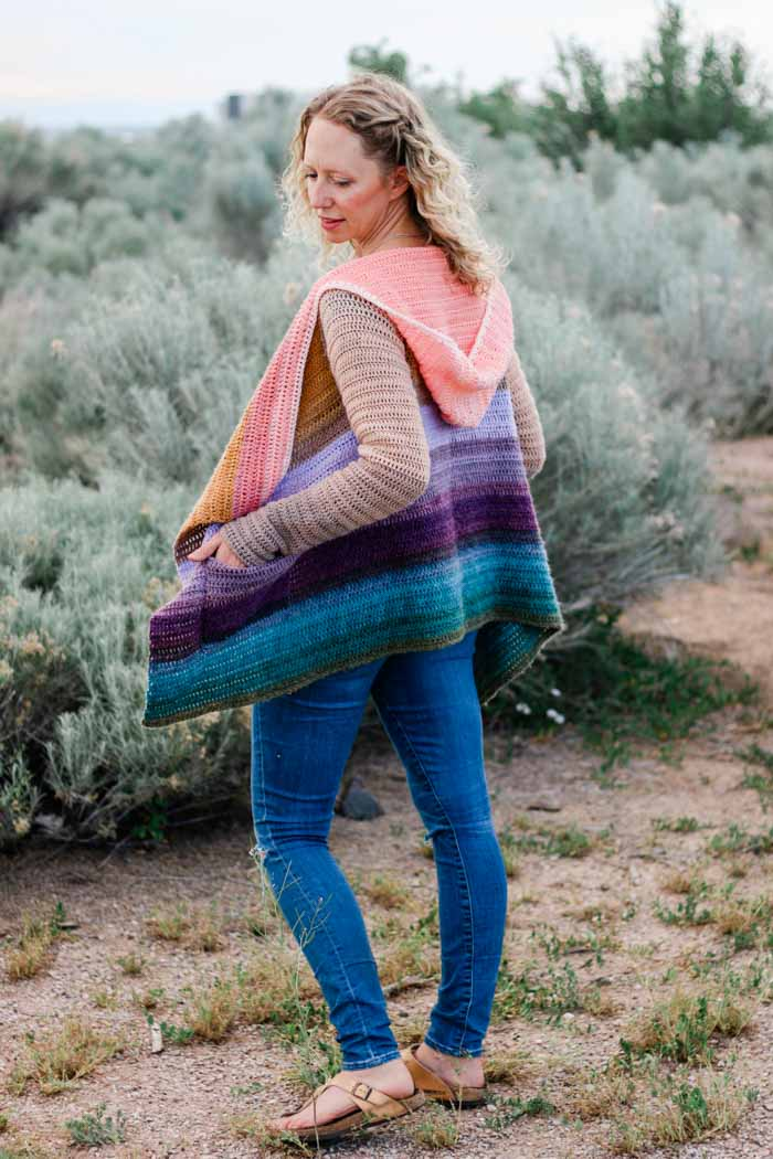 Woman standing in desert wearing a hooded rainbow cardigan in muted colors.