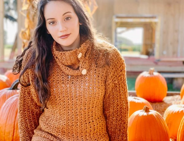 Girl sitting amongst pumpkins wearing an easy, crochet pullover sweater using Lion Brand Jeans yarn in the color Top Stitch.