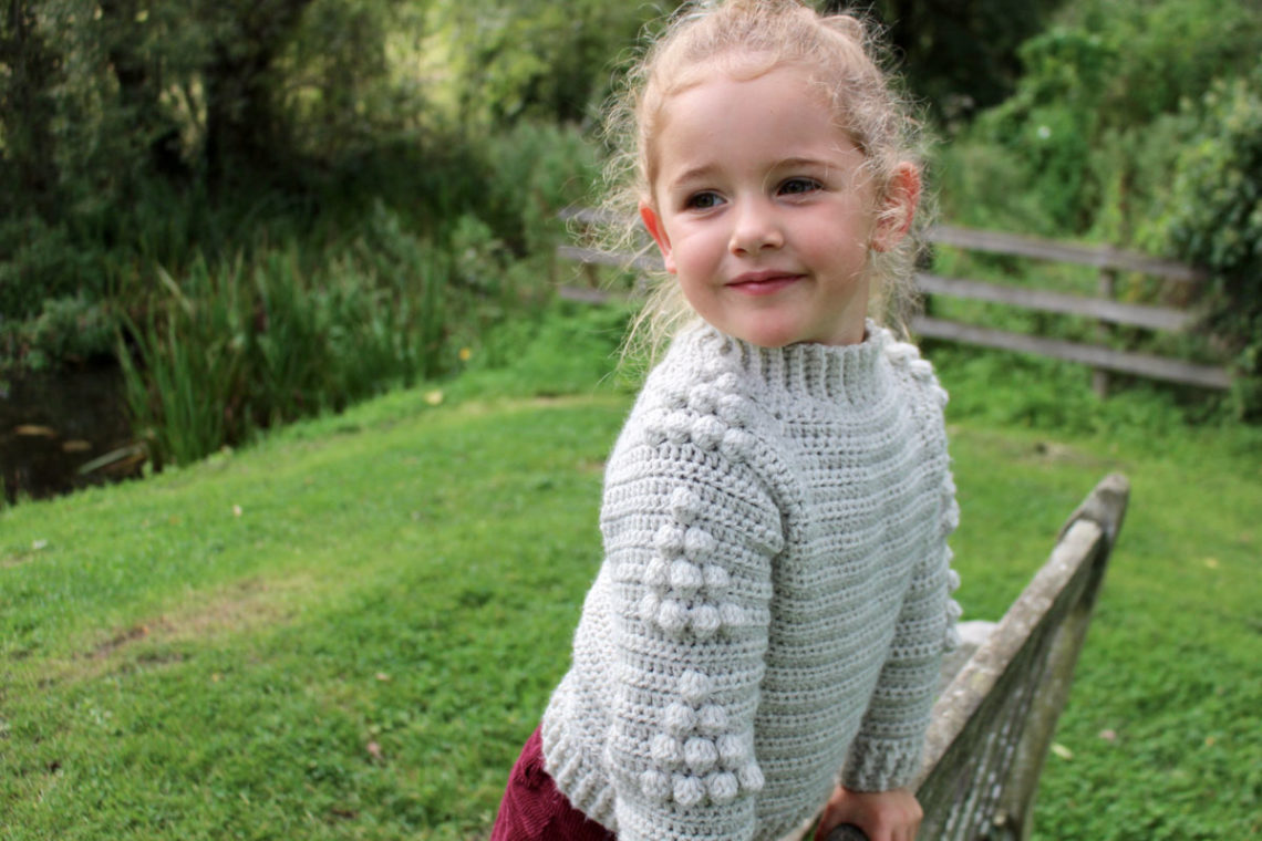 Young girl in green grass leaning on a bench. She is wearing a crochet pullover sweater, and the sleeves show a tree bobble motif. Free pattern and tutorial.