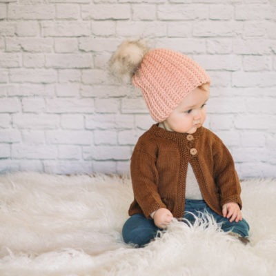 An adorable baby girl wearing a crochet hat with a fur pom pom.