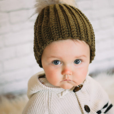 Adorable baby wearing a handmade crochet hat with a fur pom pom.