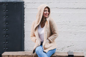 Woman sitting on a bench wearing a hooded crochet jacket made from Lion Brand Baby Soft Boucle yarn.