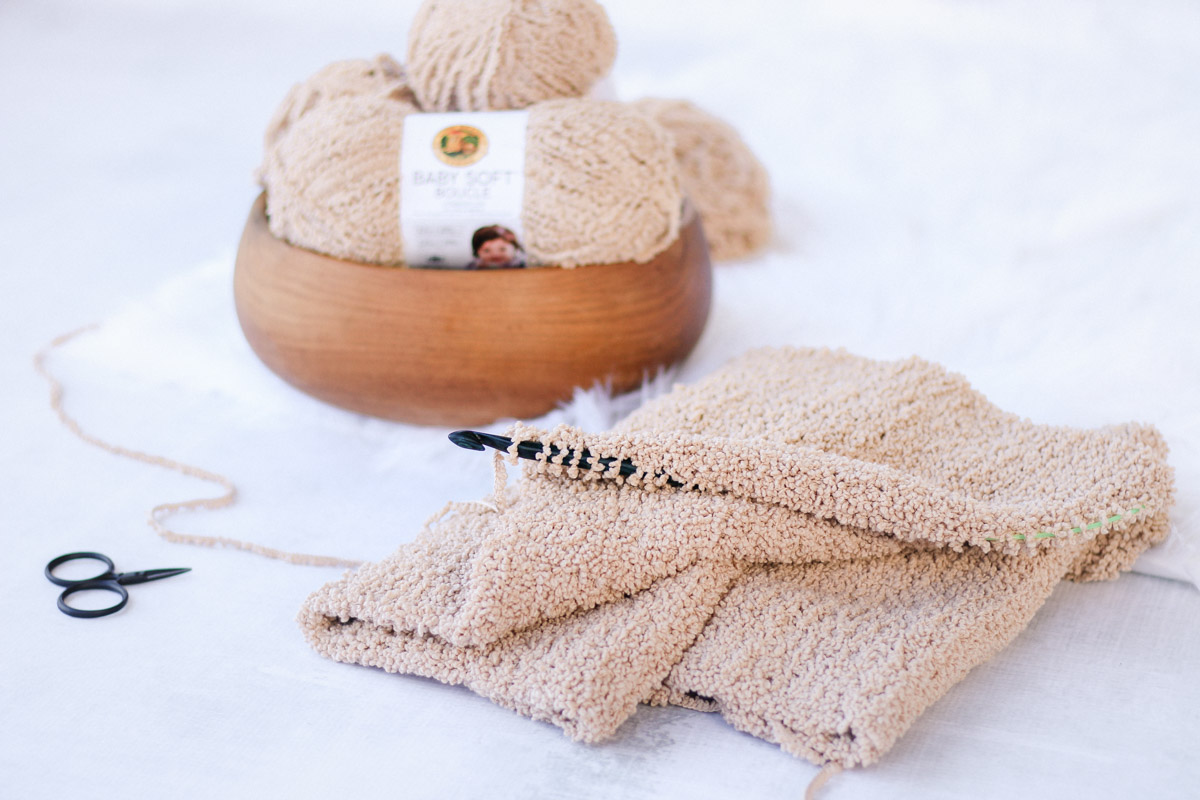 Fuzzy free crochet sweater pattern that looks like fleece made with Lion Brand Baby Soft Boucle yarn in the color Tan.