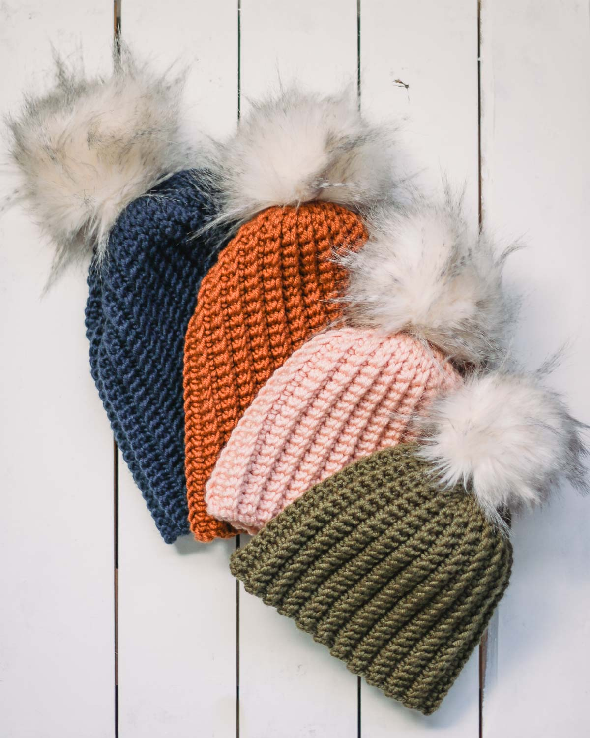 Four ribbed crochet beanies with fur pom poms laying on a white wood background. Hats in sizes baby-adult.
