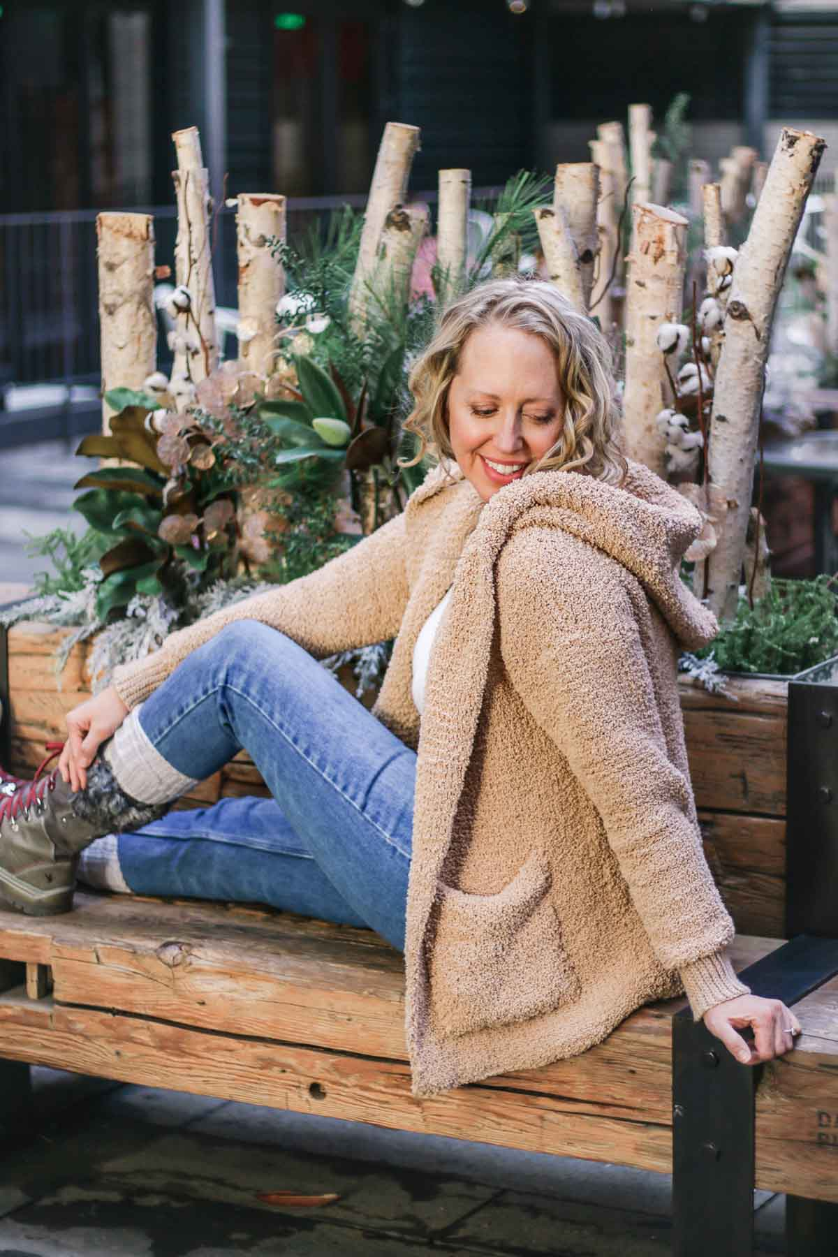 A woman sitting on a bench wearing a crochet sherpa sweater jacket with beautiful crochet sl st ribbing that looks knit.