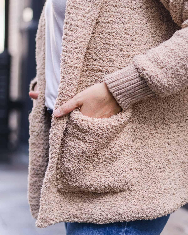 Woman's hand in a fuzzy crocheted sherpa sweater pocket.