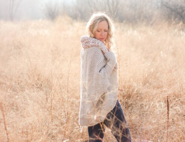 Woman standing in tall grass wearing the Backcountry Cardigan, which is a free crochet pattern from Make and Do Crew.