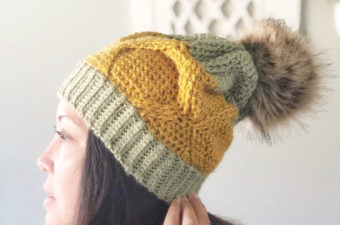 Woman wearing a pineapple-themed crochet hat with cables.