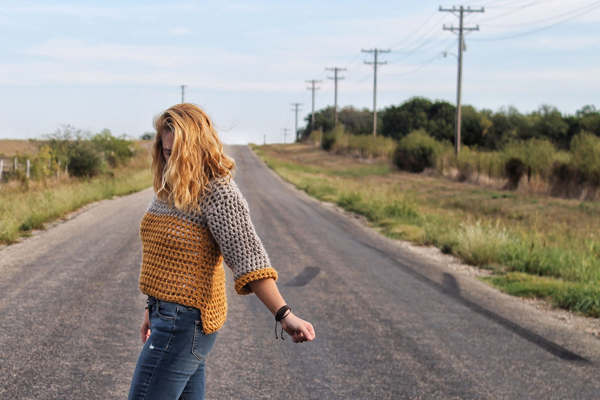 Girl standing in road surround by grass. She is wearing a gray and mustard yellow high-low crochet sweater. Free crochet pattern for an easy sweater.