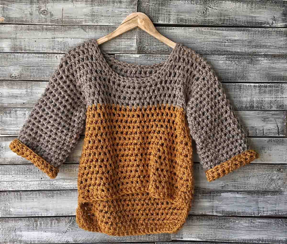 Crochet high-low sweater with 3/4 length sleeves hanging on a hanger. Made with gray and mustard yellow Lion Brand yarn.