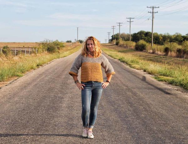 Girl standing in road surrounded by fields, wearing a cropped crochet sweater with 3/4 length sleeves.