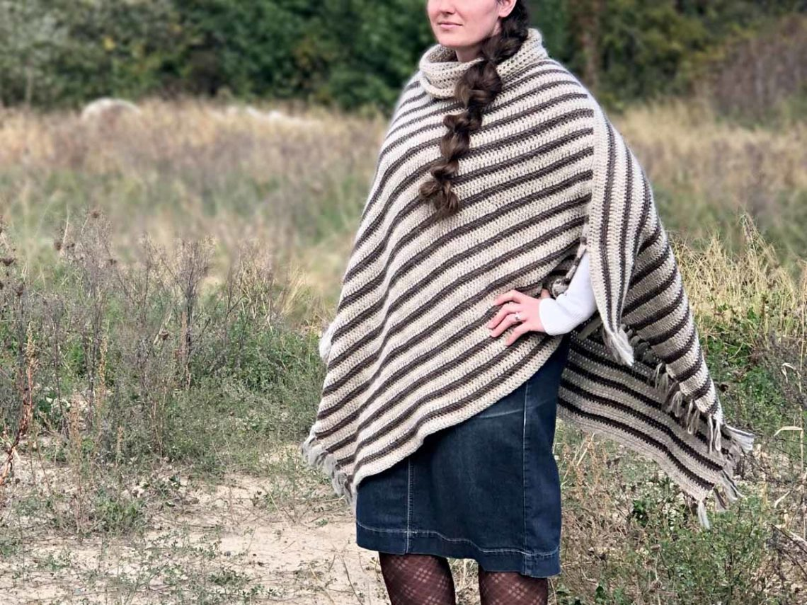 Women standing in field with her hand on her hip. She is wearing a striped crochet poncho with fringe, a dark denim skirt, and black tights.