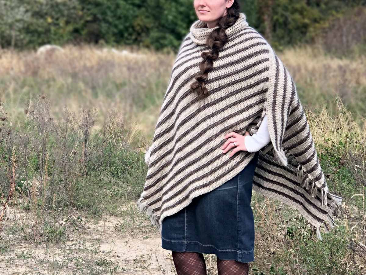 Woman wearing a crochet poncho with fringe standing in an open field.