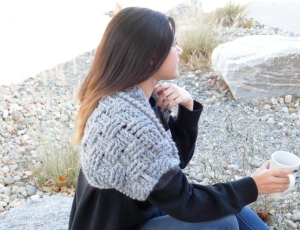 Women with long dark hair sitting on a rock, facing away from the camera and holding a white mug. She is wearing blue jeans, a long-sleeved blank shirt, and a chunky gray crochet bolero shrug.