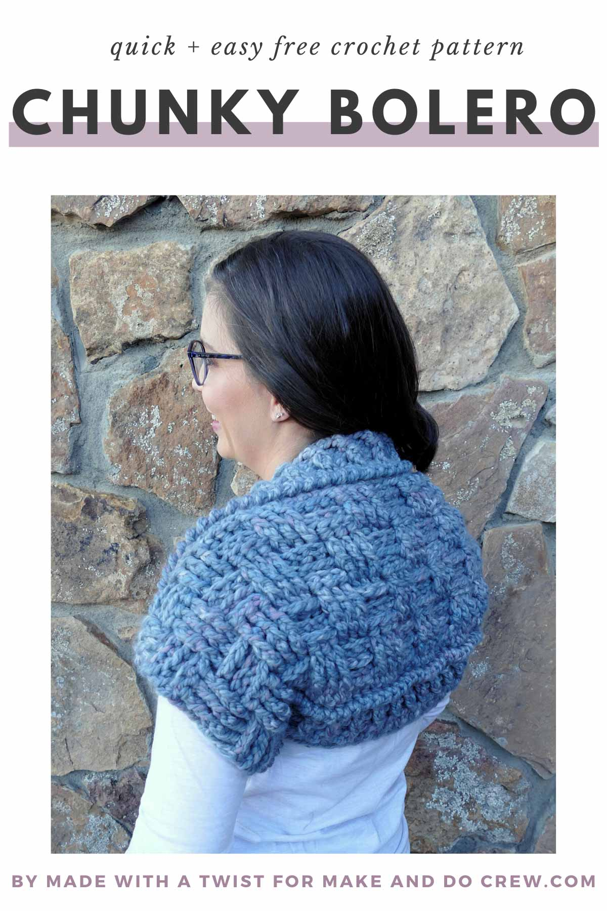 Women with long, dark hair standing in front of stone wall. She is wearing glasses and a white long sleeved-shirt. Over the white shirt, she is wearing a chunky crochet shug, made using Lion Brand yarn.