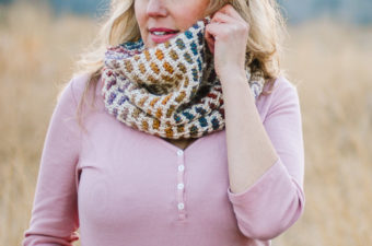 Woman wearing Tunisian crochet cowl scarf with a subtle rainbow design. Good crochet pattern for pride week.