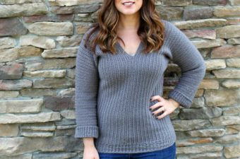 Girl with long brown hair, standing in front of brick wall, wearing a gray crochet v-neck sweater.