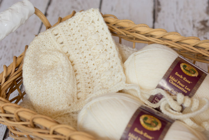 Free crochet pattern for a classic gender neutral baby bonnet, using Lion Brand Yarns Sock-ease yarn.