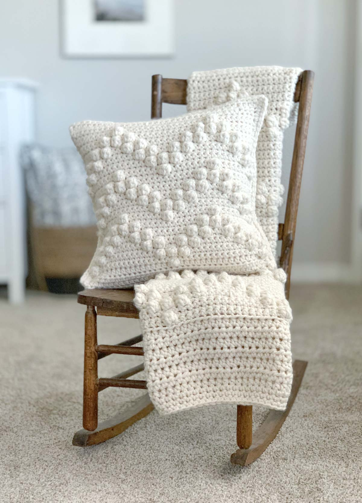 Cream colored crochet blanket and pillow on rocking chair.