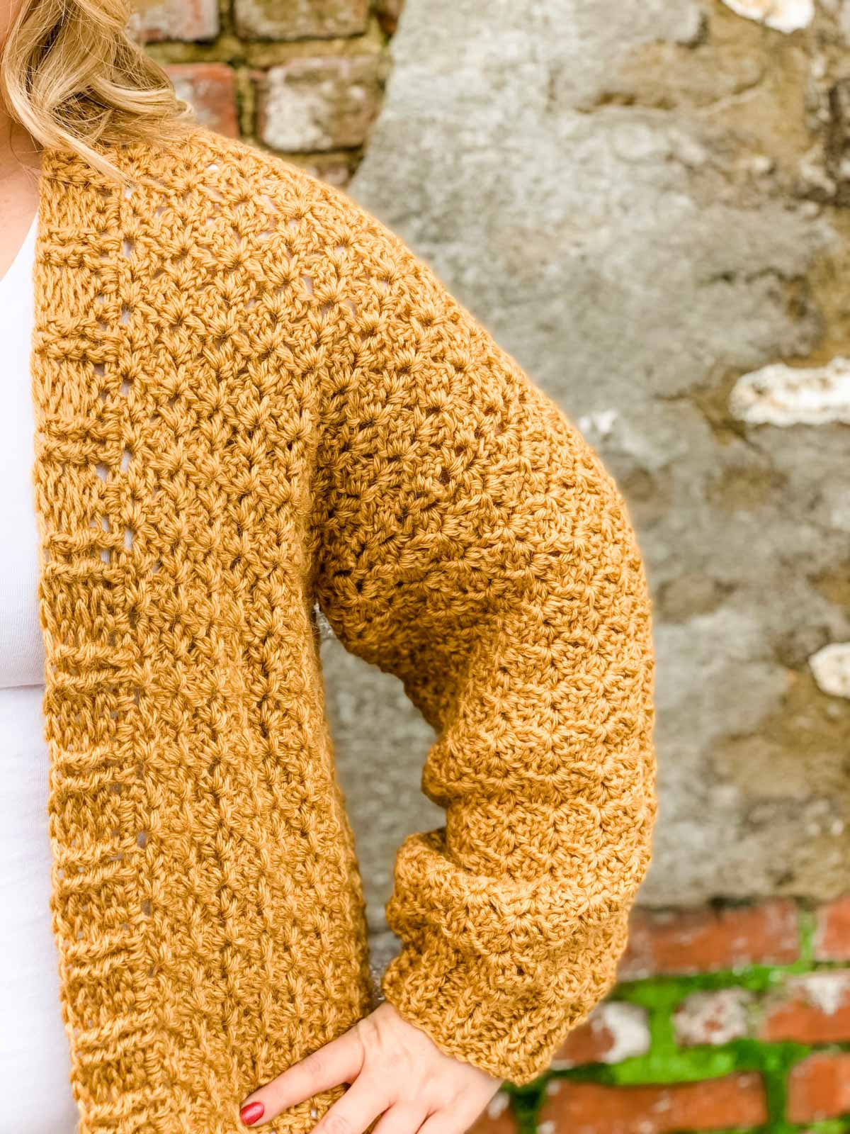 Woman standing in front of brick wall with a white shirt and mustard yellow crochet cardigan. Photo is zoomed in on her shoulder/arm area to show a close-up of the cardigan. Free crochet cardigan pattern with almost no seaming.