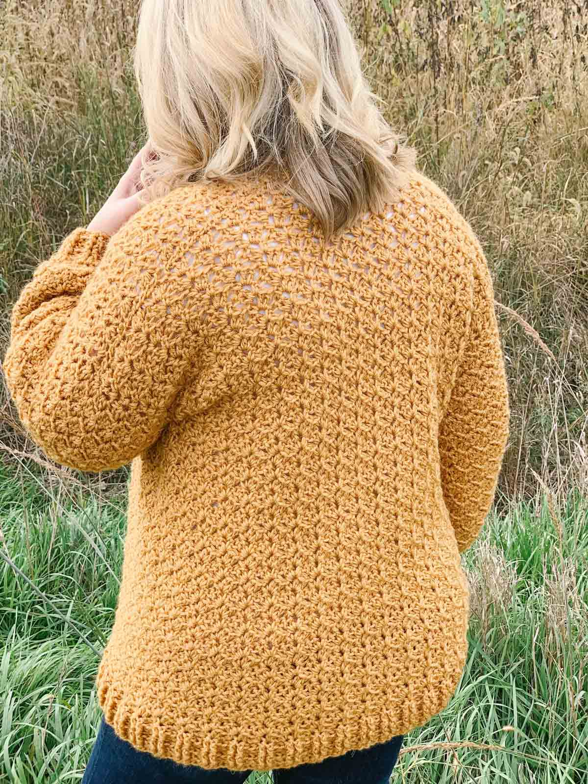 Woman with blonde hair standing in field with a mustard yellow crochet cardigan on.
