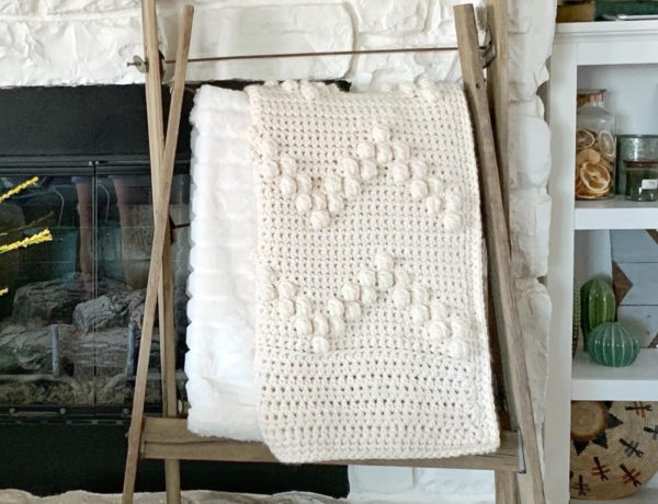 Cream colored crochet bobble blanket displayed on a blanket ladder in front of a fireplace.