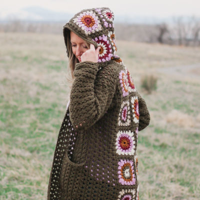 Woman standing in a field of granny wearing a vintage style crochet granny square sweater similar to the cardigan Rebecca Pearson wore on This Is Us.
