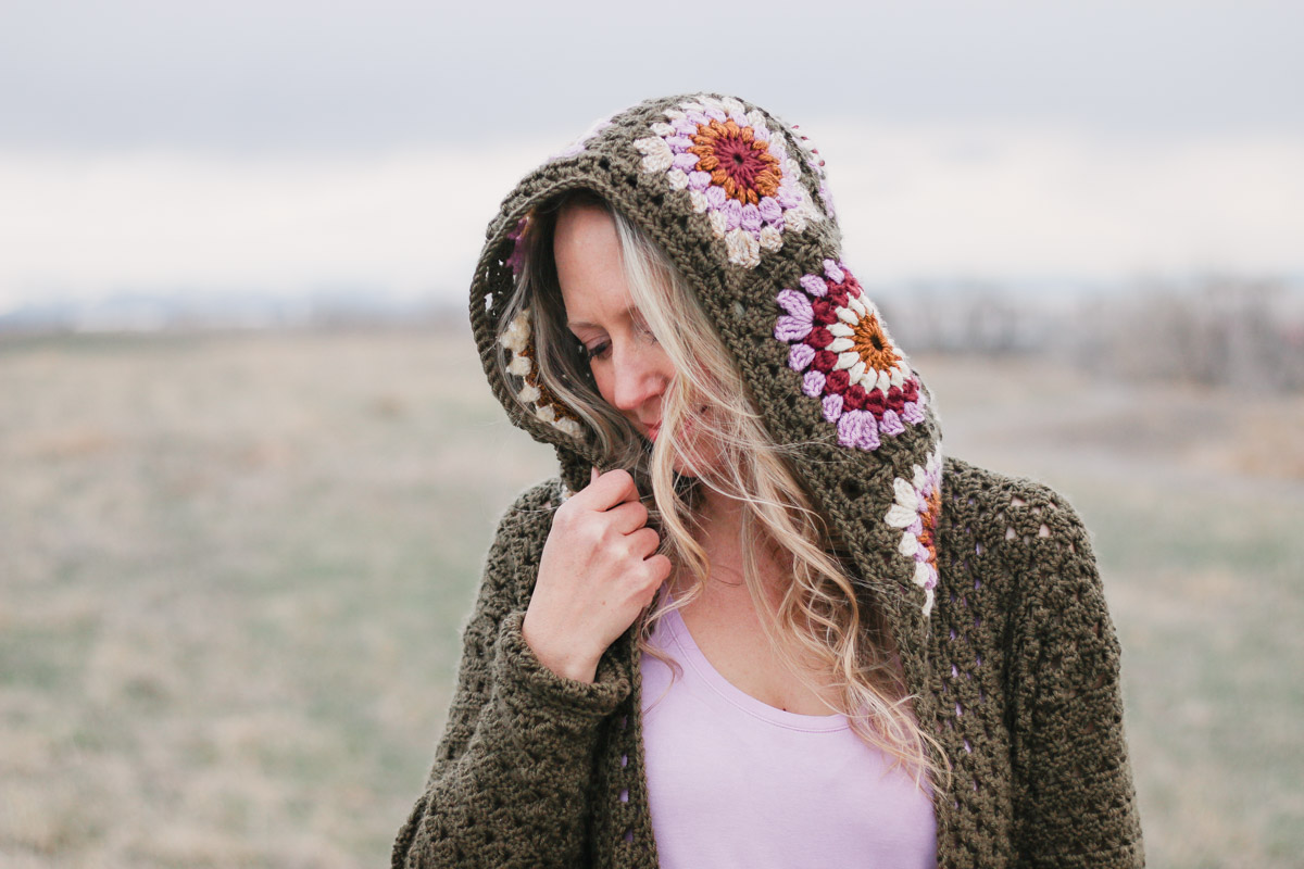 A blonde woman wearing a hooded crochet sweater featuring retro crochet granny square motifs in modern colors of Lion Brand Basic Stitch yarn.