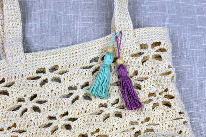 A white lace crochet purse with tassels attached to the strap.