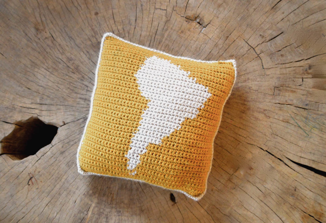 Crochet square pillow, on the front pillow square is a map outline of South America.