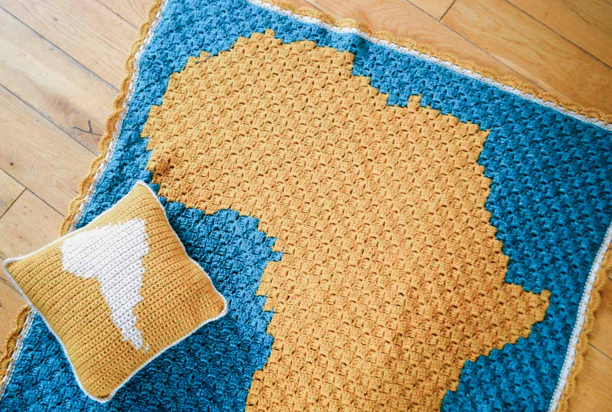 A corner to corner crochet blanket pattern with the silhouette of Africa on it.