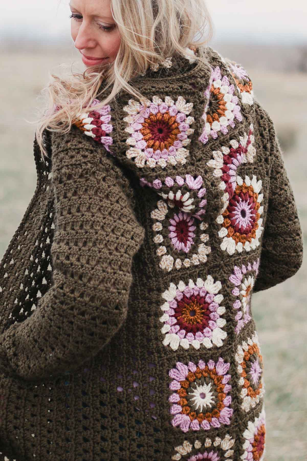 The back of a vintage-looking crochet granny stitch cardigan sweater with a hood.